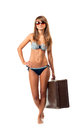 Full length portrait of a beautiful young woman posing in a biki bikini and sunglasses with suitcase hand on white background Stock Images