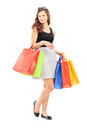 Full length portrait of a beautiful young woman posing with shop shopping bags isolated on white background Stock Photography