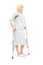 Full length portrait of a blond female patient in hospital gown with crutches isolated on white background Royalty Free Stock Photo