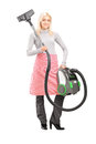 Full length portrait of a blond housewife holding a vacuum clean Stock Images