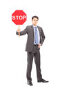 Full length portrait of a businessman holding a stop sign against white background Stock Photo