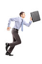 Full length portrait of a businessman running with a briefcase isolated on white background Royalty Free Stock Images