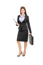 Full length portrait of a businesswoman with clipboard holding a suitcase isolated against white background Royalty Free Stock Image