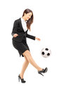 Full length portrait of a businesswoman in high heels kicking a soccer ball isolated on white background Stock Photography