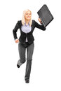 Full length portrait of a businesswoman running with a briefcase and looking at camera isolated on white background Royalty Free Stock Photos