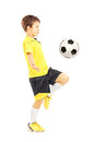 Full length portrait of a child in sportswear joggling with a ba soccer ball isolated on white background Stock Images