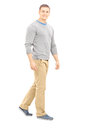 Full length portrait of a confident casual guy walking and looki looking at camera isolated on white background Royalty Free Stock Photo