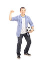 Full length portrait of an euphoric sport fan holding a ball soccer and cheering isolated on white background Royalty Free Stock Image