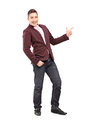 Full length portrait of a fashionable smiling guy pointing with hand isolated on white background Royalty Free Stock Photos