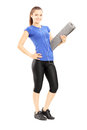 Full length portrait of a female athlete holding a mat isolated against white background Royalty Free Stock Photos
