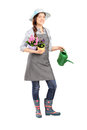 Full length portrait of a female gardener holding flower pots and watering can isolated on white background Royalty Free Stock Photo