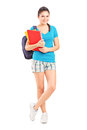 Full length portrait of a female student with backpack holding notebooks isolated on white background Stock Photos