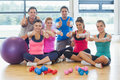 Full length portrait of fitness class gesturing thumbs up at a bright exercise room Stock Photography