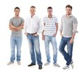 Full length portrait of group of young men wearing jeans looking at camera smiling Royalty Free Stock Images