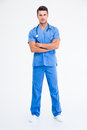 Full length portrait of a handsome male doctor standing with arms folded isolated on white background Royalty Free Stock Photos
