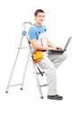 Full length portrait of a handy man with a laptop sitting on a l ladder isolated white background Stock Images