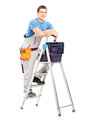 Full length portrait of a handy man posing on a ladder isolated white background Royalty Free Stock Image