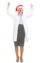 Full length portrait of happy doctor woman in santa hat rejoicing success Stock Photography