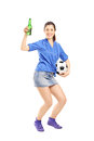 Full length portrait of a happy female fan holding a beer bottle and soccerball isolated against white background Royalty Free Stock Image