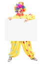 Full length portrait of a happy male clown pointing on a panel Stock Photo