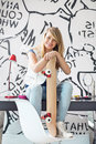 Full-length portrait of happy teenage girl with skateboard sitting on study table at home Royalty Free Stock Photo