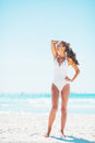 Full length portrait of happy young woman relaxing on beach in white swimsuit Stock Image