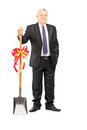 Full length portrait of an investor holding a shovel with ribbon on it and looking at camera isolated on white background Royalty Free Stock Image
