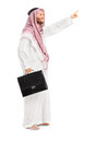 Full length portrait of a male arab person pointing holding leather suitcase and isolated on white background Stock Photography