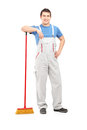 Full length portrait of a male cleaner holding a broom Royalty Free Stock Images