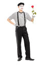 Full length portrait of a male mime artist holding a rose flower isolated on white background Royalty Free Stock Photography