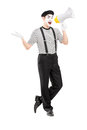 Full length portrait of a male mime artist speaking at loudspeak loudspeaker and looking camera isolated on white background Stock Photography