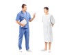 Full length portrait of a male patient in a hospital gown and medical practitioner during a discussion isolated on white Royalty Free Stock Images