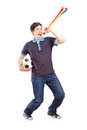 Full length portrait of a male sport fan holding a football and horn isolated on white background Royalty Free Stock Image