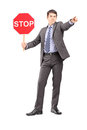 Full length portrait of a man in suit holding a stop sign isolated on white background Stock Photos