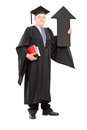 Full length portrait of a mature man in graduation gown holding big black arrow pointing up isolated on white background Royalty Free Stock Images