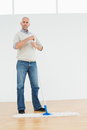 Full length portrait of a mature man standing with a mop in bright room Royalty Free Stock Photo