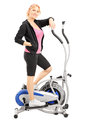 Full length portrait of a mature woman athlete on a cross traine trainer fitness machine isolated white background Royalty Free Stock Image