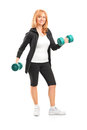 Full length portrait of a mature woman lifting up dumbbells Royalty Free Stock Photography