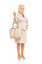 Full length portrait of a mature woman posing with a purse bag blond isolated against white background Royalty Free Stock Images