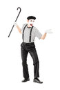 Full length portrait of a mime artist holding a cane and gesturi gesturing isolated on white background Stock Photos