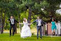 Full length portrait of newlywed couple with bridesmaids and groomsmen jumping in green sunny park Stock Image