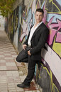 Full length portrait of posing man with suit jacket on graffiti wall Royalty Free Stock Images