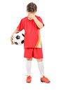 Full length portrait of a sad boy with soccer ball isolated on white background Stock Photography
