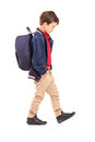 Full length portrait of a sad school boy walking isolated on white background Stock Photos