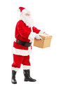 Full length portrait of a santa claus giving a box to someone isolated on white background Stock Photo