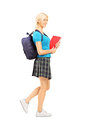 Full length portrait of a schoolgirl holding textbooks and backp backpack walking isolated on white background Royalty Free Stock Photo