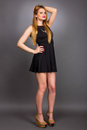 Full length portrait of sexy young blonde woman wearing a mini black dress against gray background Stock Image