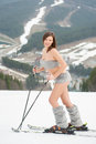 Sexy beautiful naked female skier skiing on the snowy slope of the mountain, wearing ski equipment