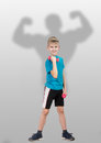 Full length portrait of smiling ten year old boy with bodybuilder s silhouette behind him on grey background Stock Photo