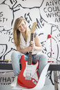 Full-length portrait of teenage girl with electric guitar sitting on study table at home Royalty Free Stock Photo